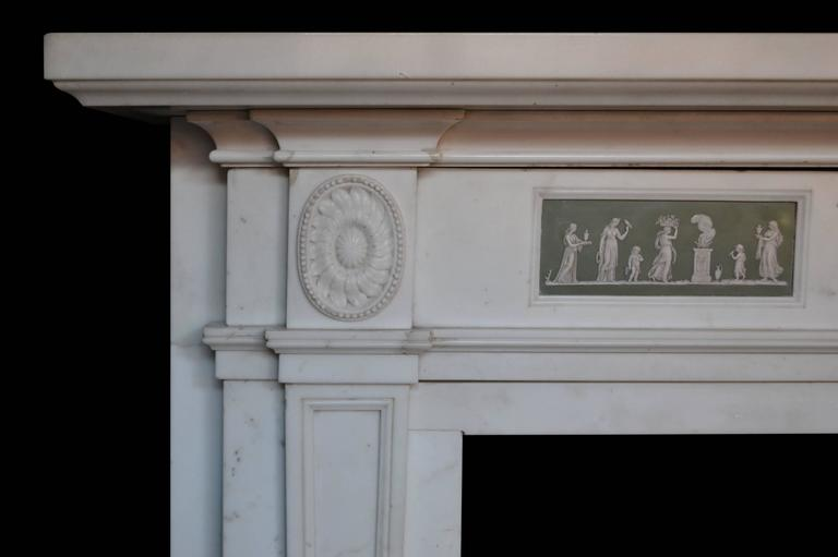 A generously proportioned mantel carved in statuary marble with two medallions and a center tablet with carvered urn. The mantel frieze features two porcelain wedgewood panel inlays. 