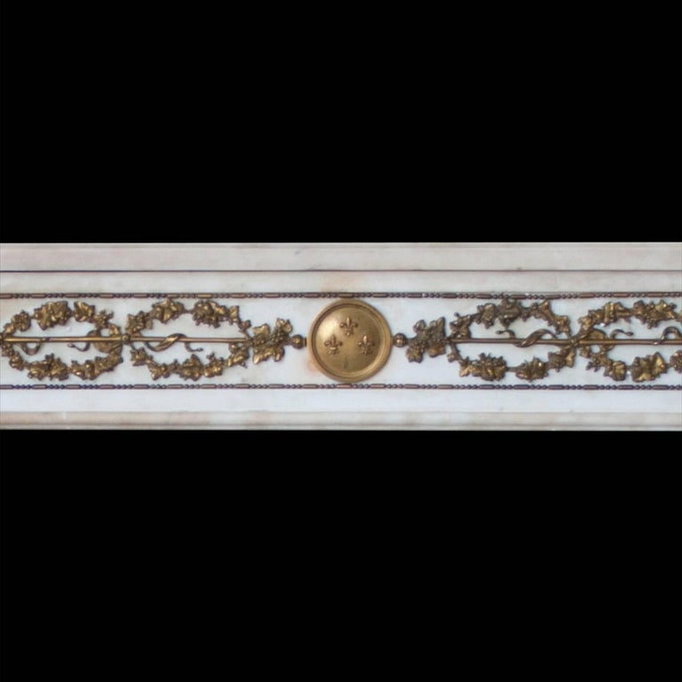 A French Empire style mantelpiece carved in Italian statuary marble with fine ormolu detailing.  Opening dimensions: 48 1/4