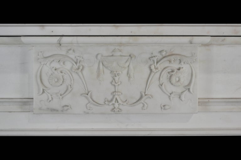 An early 19th century English mantelpiece of restrained and elegant form, incorporating later elements and repairs, in Italian statuary marble with tapering fluted pilasters headed by corner blocks carved with anthemion, a neoclassical centre tablet
