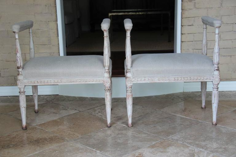 A rare pair of 19th century Swedish Gustavian window seat stools with padded armrests, newly upholstered in Fine de Le Cuona Belgian linen, Urban Linen, color stone. The seat frame features beautifully carved acanthus leaves that are repeated on the