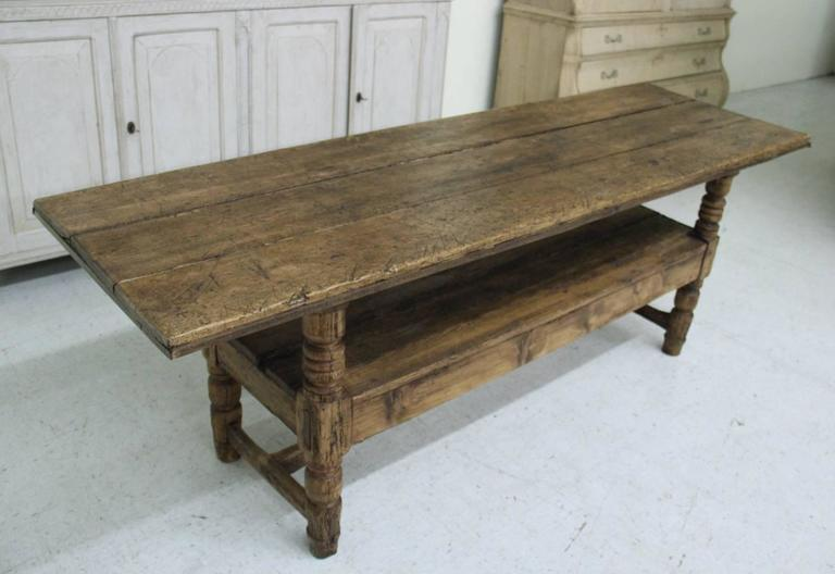 A 19th century Spanish Bishop's bench in the Provincial style that has been converted to a console table. The table has a plank top and turned legs with center stretcher below the lower shelf.