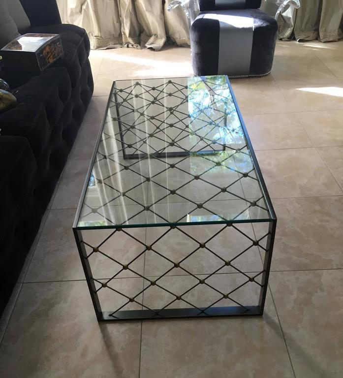 A stunning pair of steel coffee tables with stainless steel and brass details by Carole Gratale. Sold separately.  Inquire for group price.    These rectangular tables have a tempered glass top and feature a lattice pattern of intersecting brass