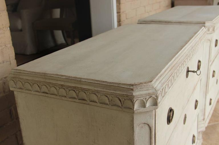 A beautiful pair of Swedish Gustavian style painted chests from the 19th century with egg and dart carving; canted corner posts; and square, fluted legs. Each chest has three drawers, brass hardware and original locks with keys.    The Gustavian