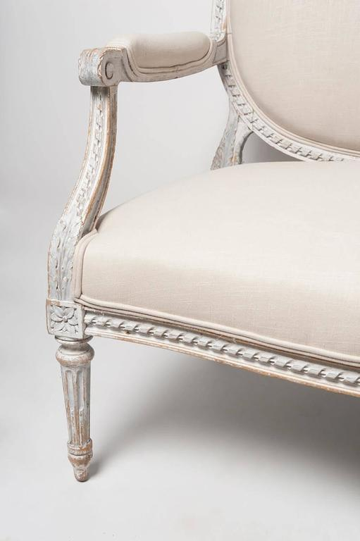 A 19th century, French, Louis XVI style oval back salon settee retaining its original painted patina, newly upholstered in a natural linen. The frame, richly carved and accented by acanthus leaves and rosettes, rests upon tapered and fluted legs. A