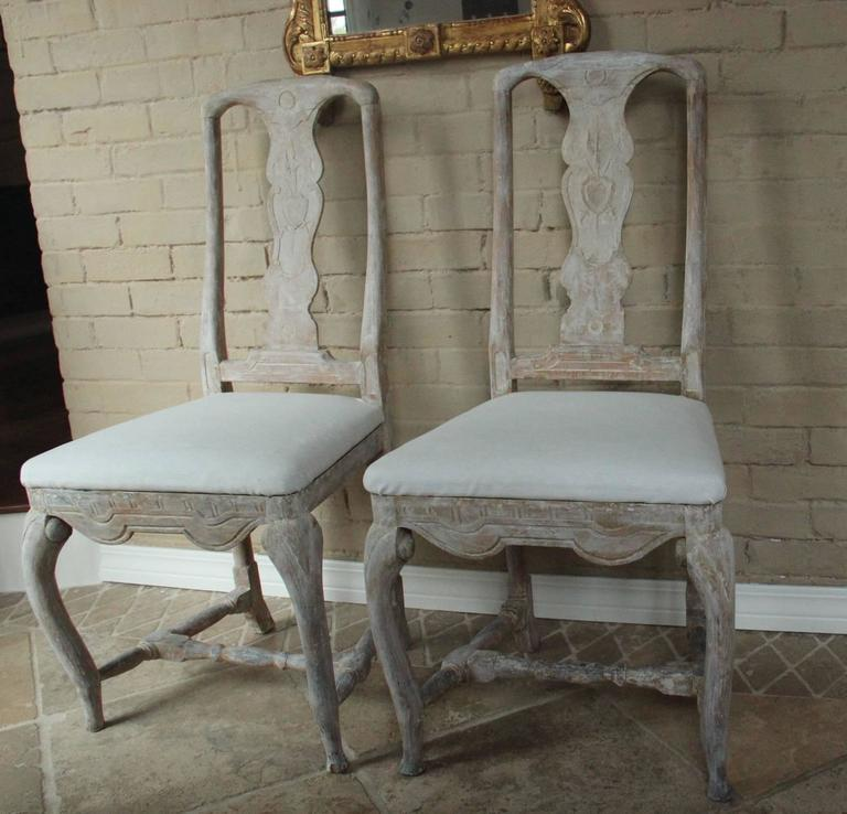 A stunning pair of 18th century, Swedish dining chairs from the Rococo period with splat backs carved with a family crest, carved and shaped seat rail, refined cabriole legs, H-shaped stretcher and slip seats. Beautifully proportioned and hand