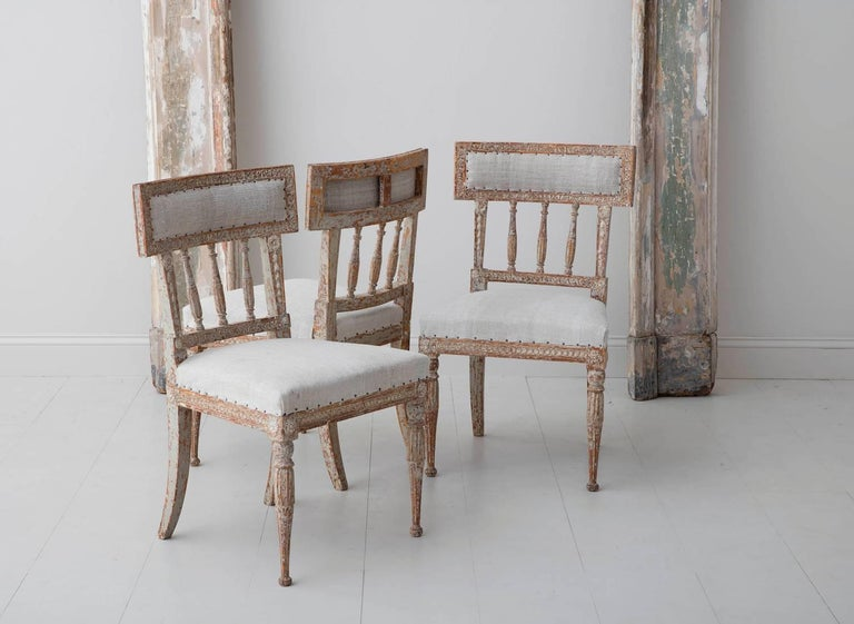 A set of six Swedish chairs from the Gustavian period in original ivory / taupe / gray paint, newly upholstered in antique linen. These beautiful chairs have curved splat backs, inspired by antique Roman