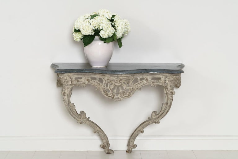 A large 18th century French console table from the Louis XV period in original paint. The original blue turquin marble top is bevelled and contoured to complement the base. The frieze is scroll-carved and pierced.