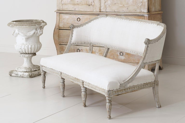 A 19th century Swedish barrel back sofa settee in the Gustavian style, newly upholstered in antique linen, circa 1850. Hand scraped to reveal the original paint. The frame features carved lion heads and bell flowers while the front legs are adorned