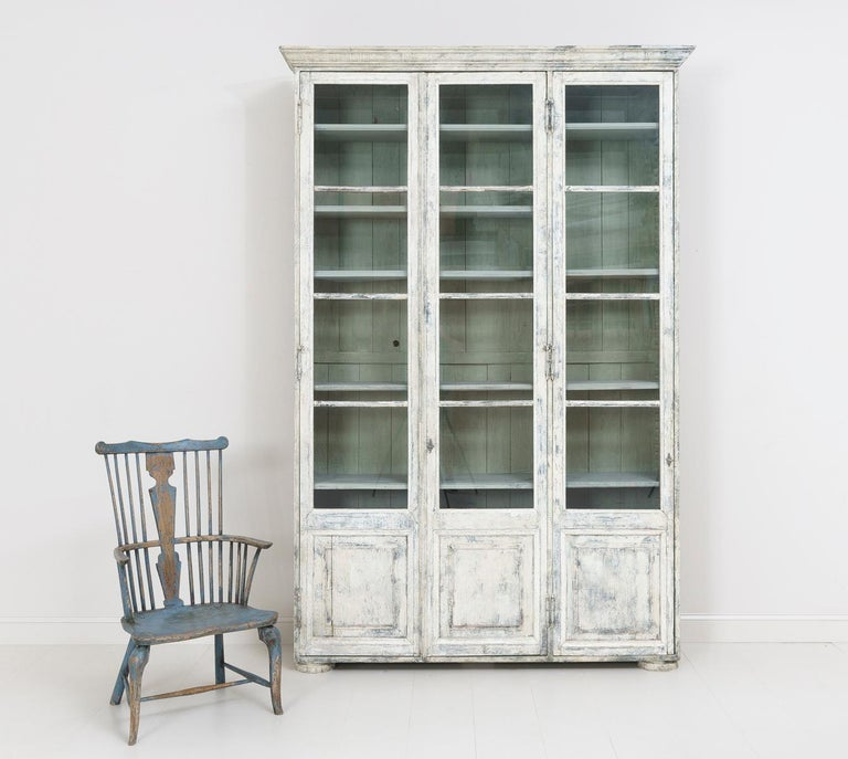 19th century French bibliothèque with original glass and adjustable shelves. This beautiful vitrine or bookcase is the perfect piece for almost any room. The exterior color is aged white with areas of blue and gray showing through. The interior is a