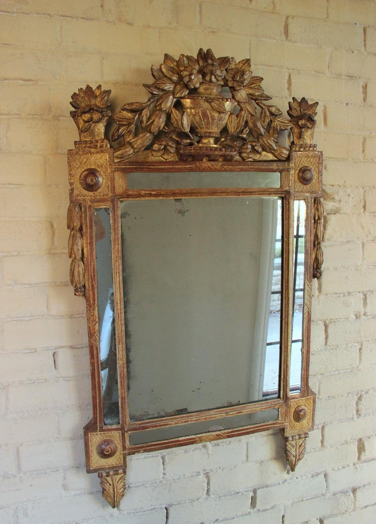 A beautifully carved French original giltwood mirror from the Louis XVI, 'Louis Seize', period with urn pediment and floral motif. Original mercury mirror plate. The carved crest features an urn filled with a bouquet of trailing flowers. The floral
