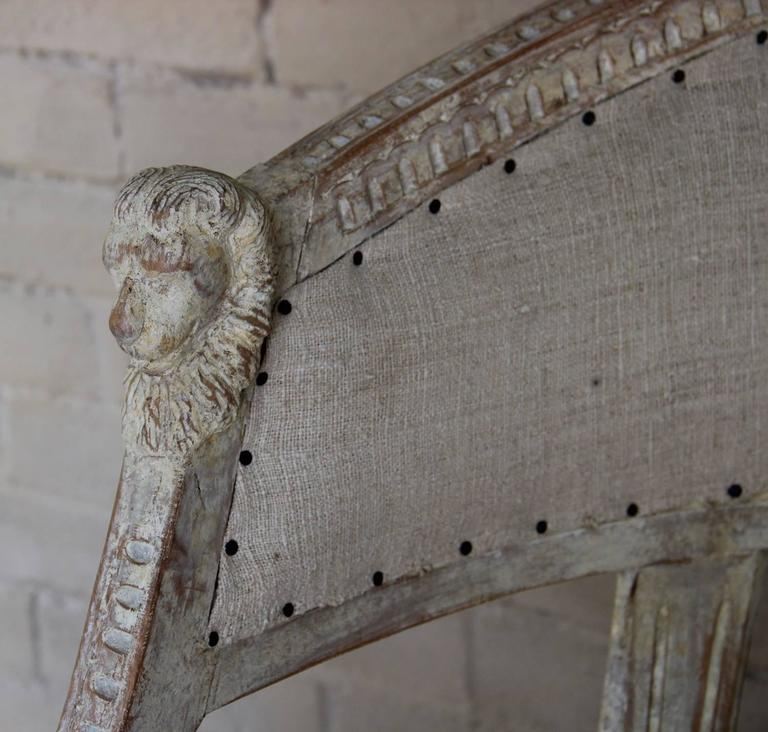 A Swedish late Gustavian pair of klismos armchairs with lightly refreshed original paint.  These stunning chairs have barrel backs with cravings of lions' heads. The frame features lamb's tongue carving throughout and the front legs are adorned with