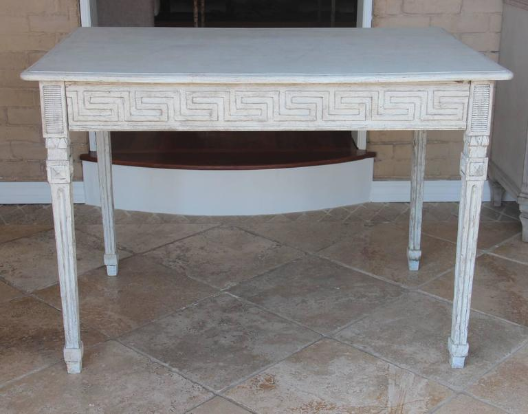 A 19th century Swedish writing desk in the Gustavian style with a soft, old white patina. There is an intricately carved apron featuring a Greek Key design on all four sides. The drawer is concealed within the apron. The table rests upon square,
