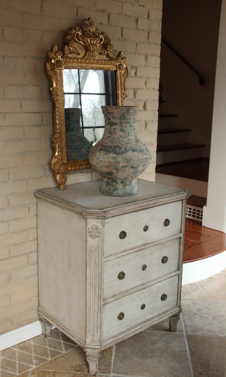 A beautiful neoclassical pair of Swedish Gustavian Style painted chests with an aged gray patina. Each chest has three drawers, brass hardware, and original locks. The corner posts are canted and fluted with carved rosettes at the top. Gustavian at