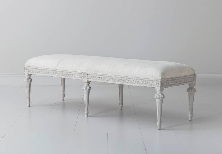 Price per piece.  Please inquire for group pricing.    A richly carved 19th century Swedish 'brother and sister' pair of painted long benches in the Gustavian style. There is a carved guilloche pattern on the seat frame and carved rosettes above