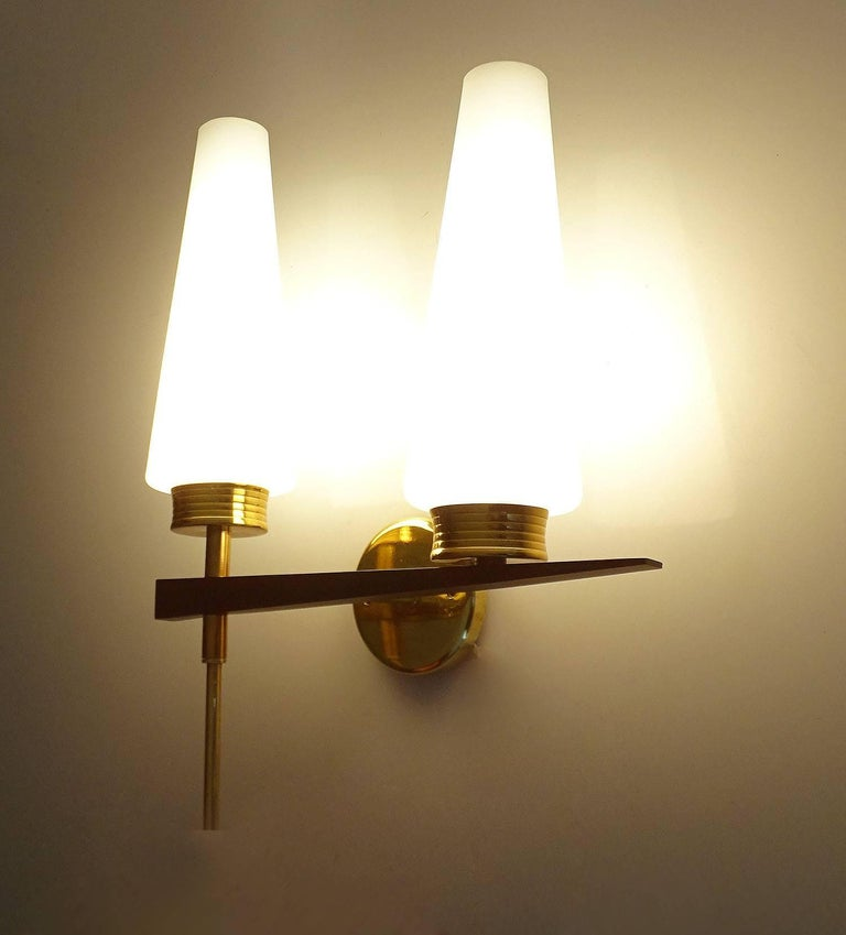 Pair of architectonic , sculptural French sconces by Maison Arlus, 1960s featuring two conical opaline glass shades mounted on a brass and black enameled structure 14.96 in. H x 11.42 in. W x 4.72 in. D 38 cm H x 29 cm W x 12 cm D Two candelabra