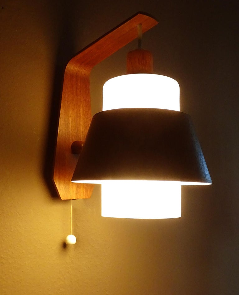 All our light´s electricals are professionally checked and tested for worldwide use Exceptional pair of large Swiss Danish modern style sconces, featuring a teak support and cylindrical opaline glass shade. With teak veneered