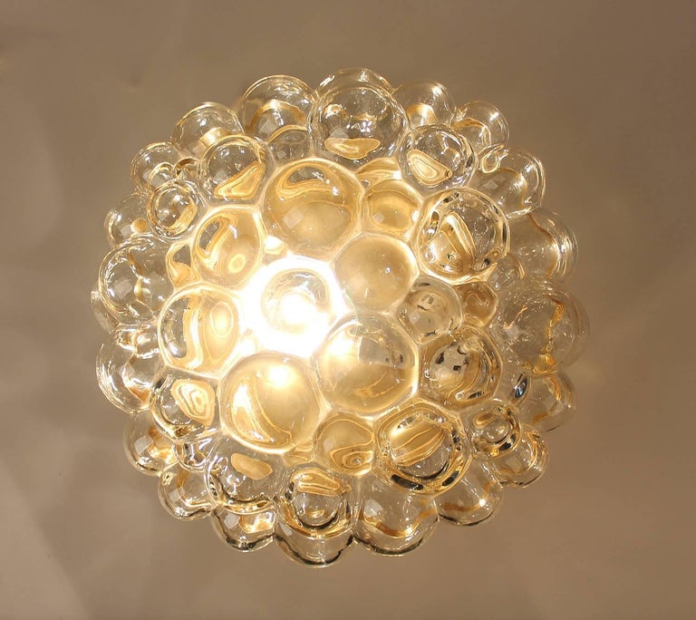 Large Limburg blown glass sconce / flush light, design by Helena Tynell, glass has slight amber color, bronze enameled base.