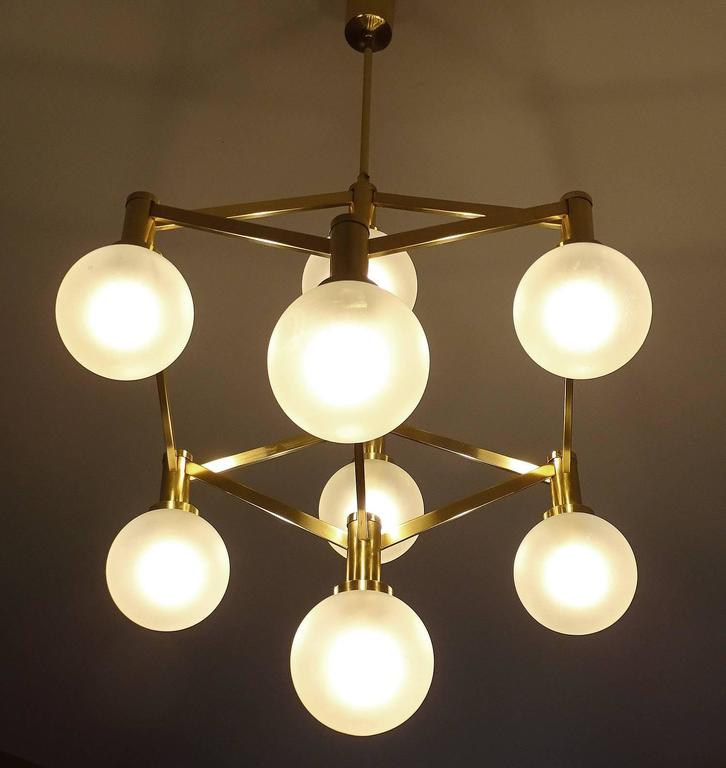 Exceptionnal Mid-Century chandelier, featuring a three dimensional brass cube structure with eight frsoted glass globe shades. Due tp the construction and the perspective effect, not one viewing angle looks identical.   Height of the structure alone