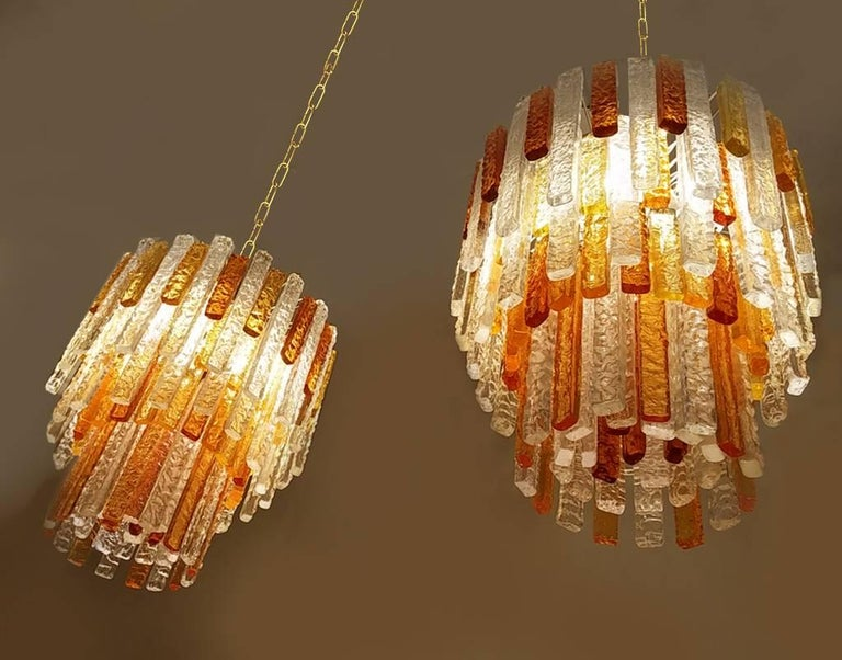 Pair of  1960s  Murano glass chandelier by Mazzega , with each 127 textured pendants in five distinct colours and two height sizes: white, light yellow, light amber, amber and dark amber tone. The number of colors pendant differs somewhat for both