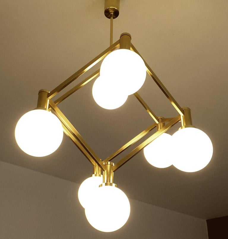 Italian mid century modern chandelier  featuring a three dimensional brass cube structure with eight opaline glass globe shades. Spectacular is the construction and the perspective effect, every viewing angle looks different.  36.61 in H x 19.68 in