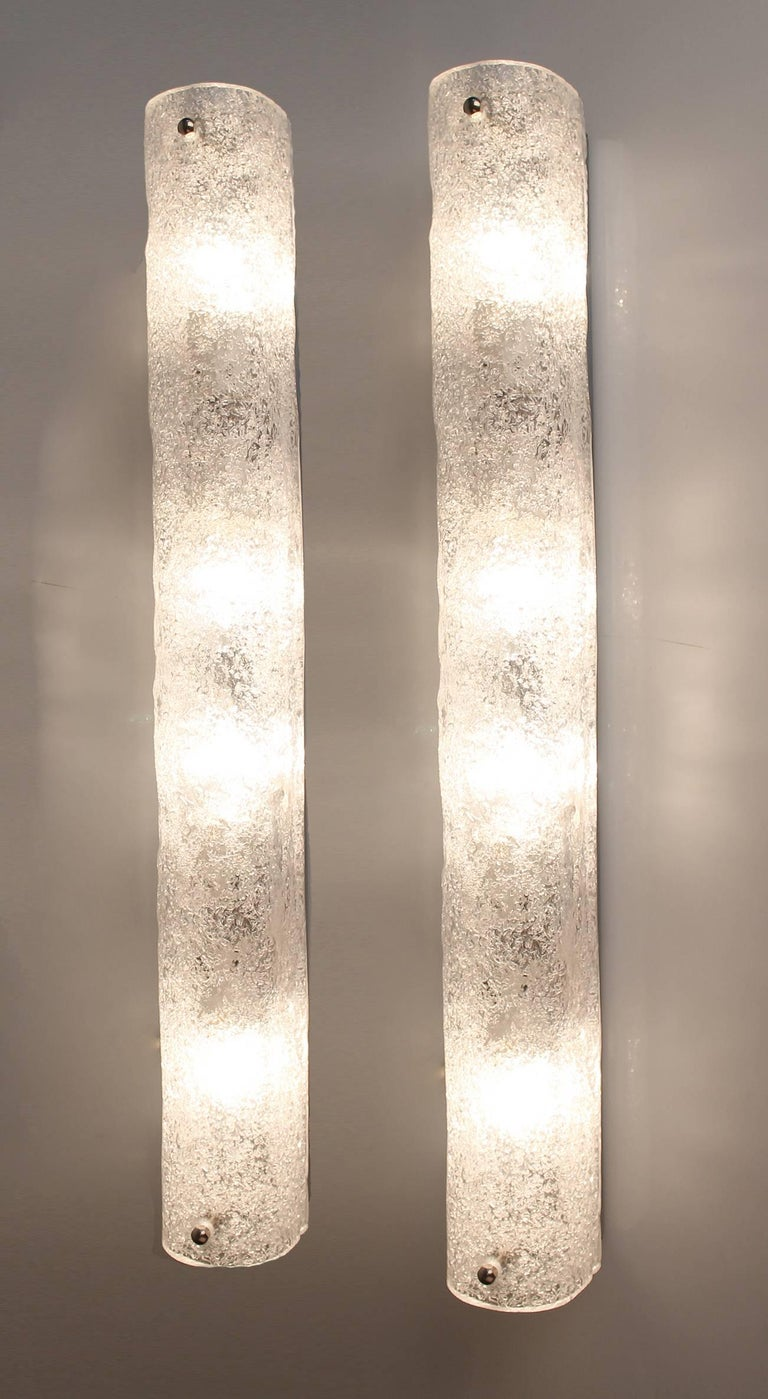 Three large mirror vanity sconces with handcrafted Murano glass shades on chrome base. 23.62 in H x 4.33 in W x 3.15 in D. 60 cm H x 11 cm W x 8 cm D Four candelabra size bulbs per light, 40 watts each     The stylish elegance an design suits  mid