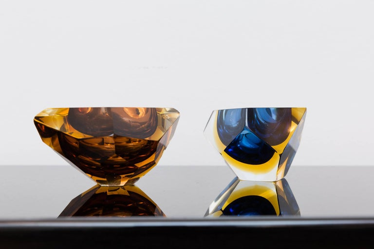 Beautiful multi-color set of two unusual faceted Bowls, Murano, Italy, circa 1960, Prod. Sommerso, different colors by orange, amber-yellow, blue, into clear glass. The vibrant colors and the different sizes make this pieces highly decorative.