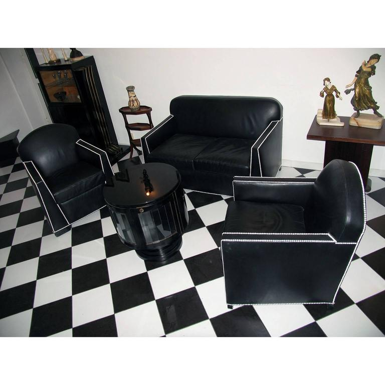 Art Deco modernist sofa and a pair of armchairs upholstered in black leather, exquisitely detailed with white nails. Wooden structure, black painted wood feet, spring upholstery and seat cushions.  Dimensions: Sofa Width 137 cm (54 in.), depth 82 cm