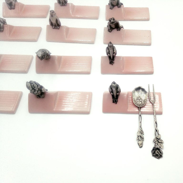 Very rare set of twelve French Art Deco silver plated knife rests mounted on pinkish glazed ceramic supports. Argit Orfevre, Paris, in the early 1930s Very decorative, exquisitely shaped, mixing the very detailed animal figures with the fine glazed