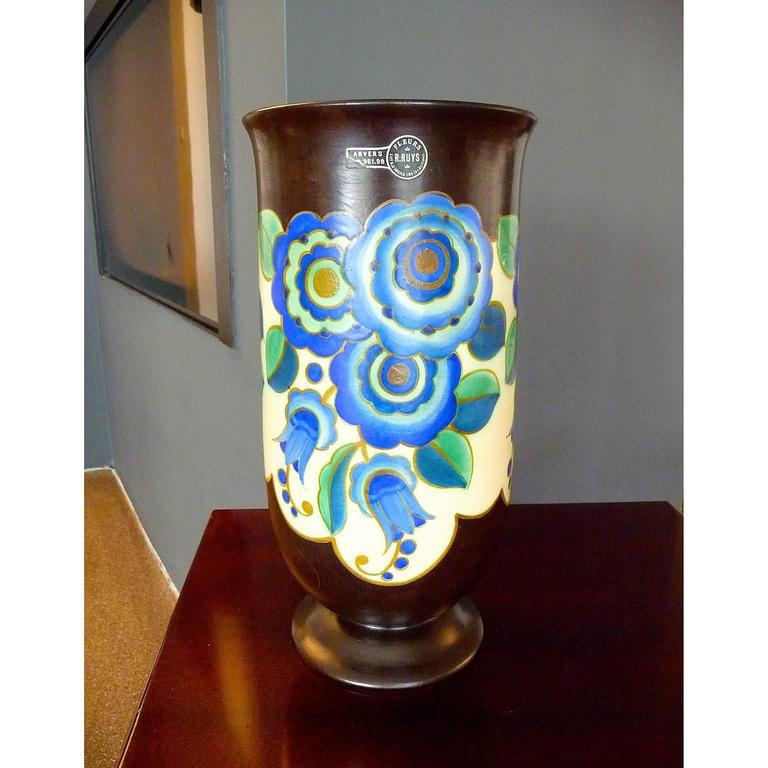 Keramis, Belgium Art Deco ceramic vase. Cylindrical shape vase on a small pedestal. Flower decor of poly-chrome enamels with gilded enhancements. Decor D2783. Form 1305. Signed. Rest of label of a shop in Anvers.  Dimensions: Diameter 17 cm