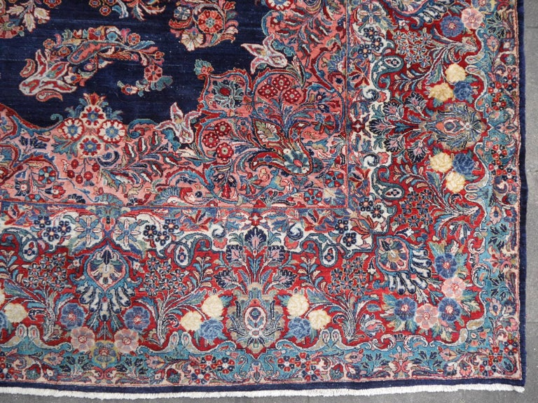 Oversize Sarouk rug. Rare blue ground Sarouk in excellent condition. Good full pile condition, vibrant colors.  This one of a kind oversized Sarouk rug has an impressive appearance. A beautiful indigo blue field contrasts with rose - pink, turquoise