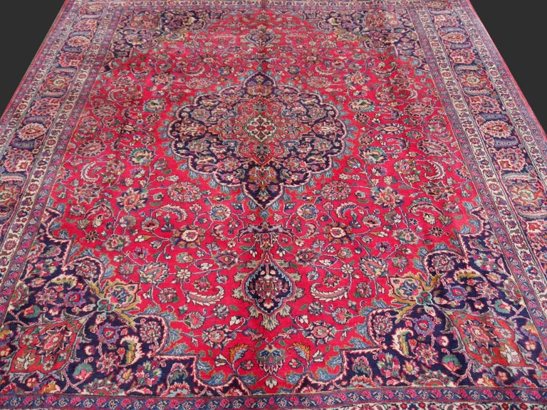 This midcentury Mashad rug was hand-knotted using wool and traditional motives. It is in very good original condition with good high pile and a silk like luster.