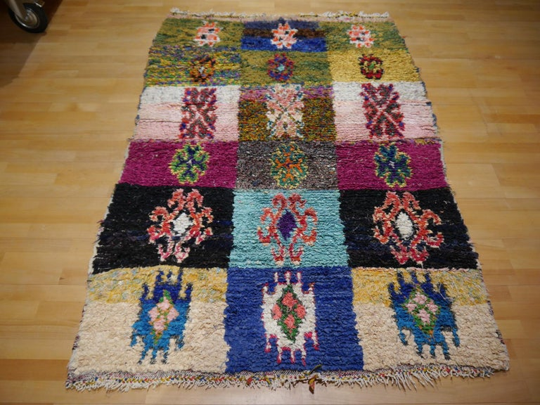 This tribal hand-knotted rug was made by a woman in the Moroccan Atlas Mountains. She upcyled textiles from skirts and wedding dresses. These are cut into small pieces and knotted into the woven structure. Typically, these rugs contain different