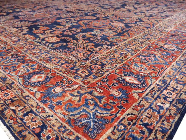 Oversize Persian Sarouk rug. Rare blue ground Sarouk in very good condition. Good pile condition, some area of lower pile, old restorations.