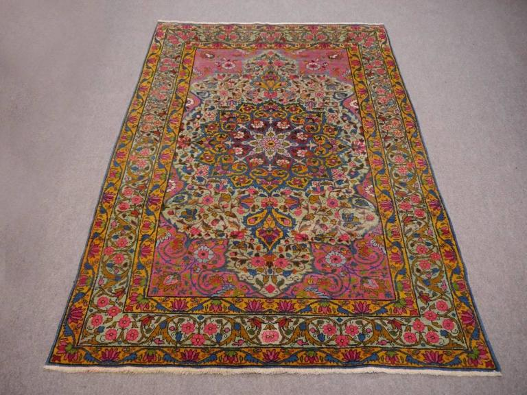 One of a kind Persian antique rug with light green background color and wild color combination. Very decorative rug for a statement in interior design, overall very good condition with some lower pile areas that give the antique look to this special