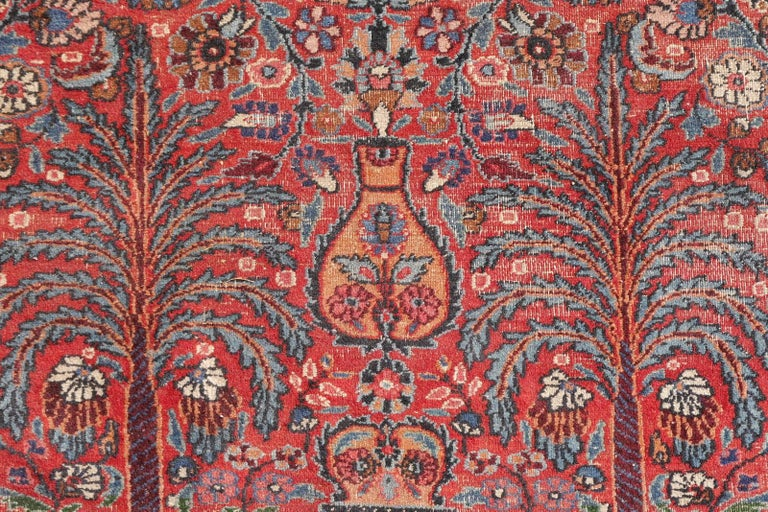 A wonderful and hard to find vintage worn rug with an ascending garden design. On a red filed, a pair of date palms, cypress and pomegranate trees are the motives at the lower end of the rug. Above a design with arabesques, flowers and lotus motives