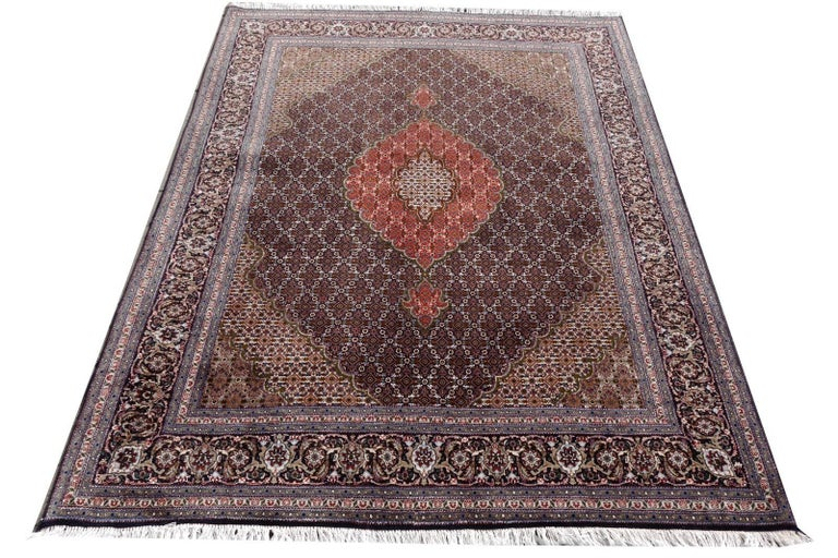 A very elegant Persian Tabriz rug, hand-knotted using fine Persian highland wool combined with silk highlights. Very fine knot count.  The black field is decorated with small diamond designs, a flower in it´s centre, guided by palmette motives.