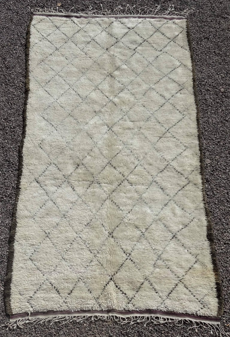 This hand-knotted vintage ivory wool rug was made by women living in the Middle-Atlas mountains in central Morocco. It is circa 30 - 40 years old and in very nice condition for it´s age. It has a wonderful soft woolen pile, knotted on a woolen