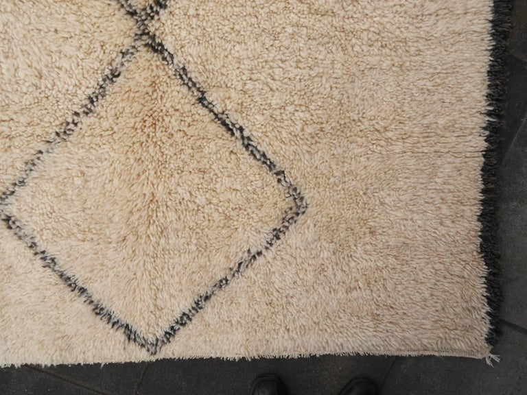 This tribal small rug was hand-knotted by women of the Beni Ourain tribe in the middle Atlas Mountains in central Morocco. These rugs are very soft and more like a blanket with pile than a heavy rug known from other counties. The pile and the