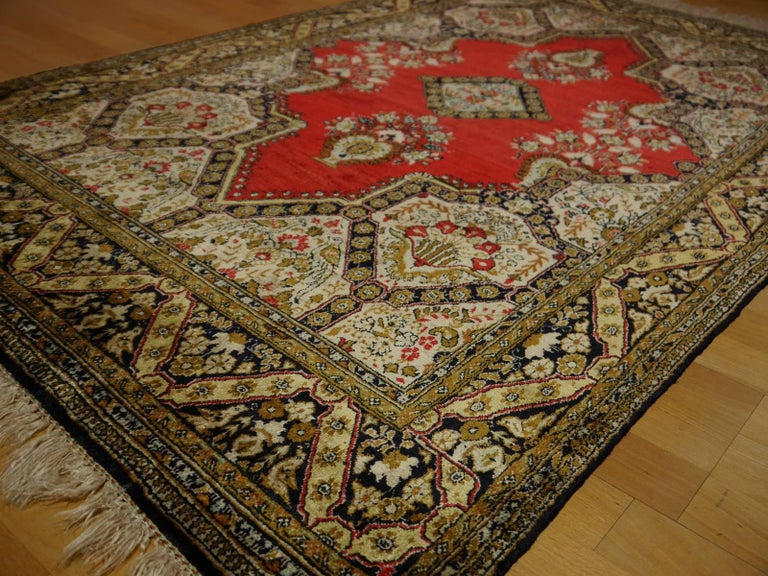 A hand-knotted vintage Persian rug. Pile and warp are made of 100% pure natural silk. The best-known silk is obtained from the cocoons of the larvae of the mulberry silkworm Bombyx Mori. It has a beautiful luster and shine. The pigments used to dye