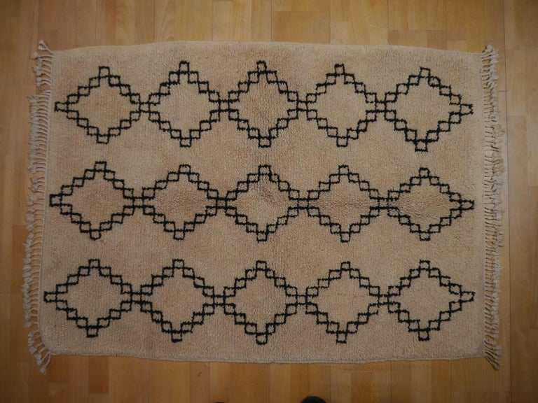 Beautiful vintage Berber rug from the Atlas Mountains. Good full pile condition, all edges original. Great patina and vintage style. Hand-knotted by a tribal woman of the Azilal tribe. Undyed wool in beige and brown.  Berber rugs and carpets are