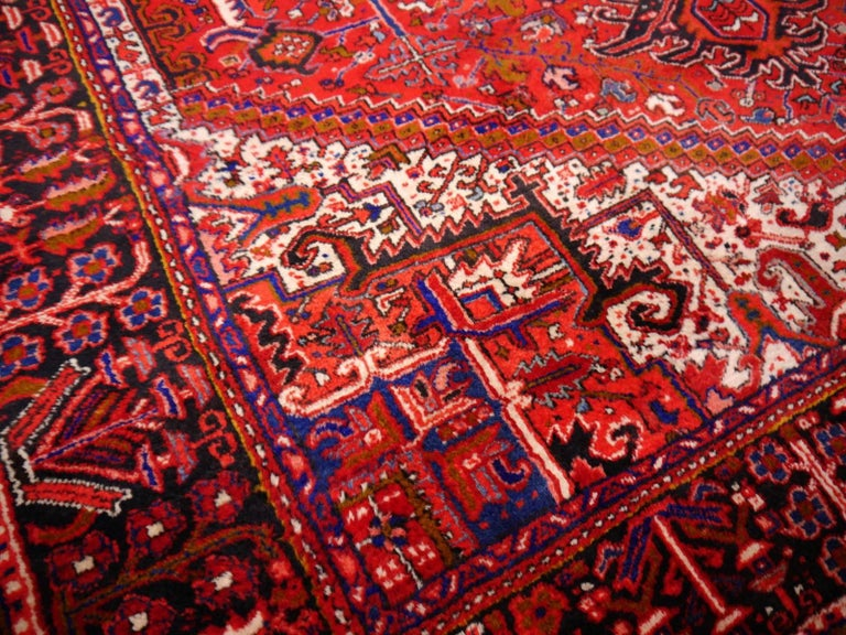 This Persian Heriz rug was hand-knotted by Artisians in north western Persia. It has a pile made of fine wool and decorative colors - red, sky blue, dark blue, wool white, dark salmon, brass - olive. The condition is excellent with flushy high pile