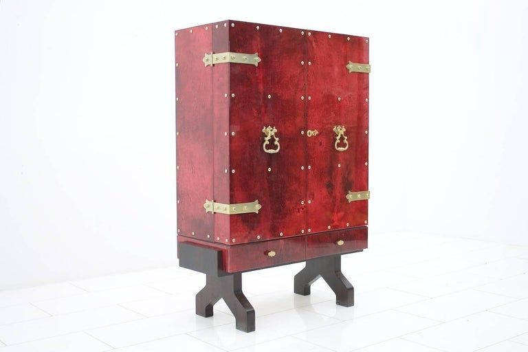 lluminated, mirrored dry bar by Aldo Tura, Italy in rare red goatskin, lacquered. Nicely brass details. The dry bar comes from the 1960s. H 131 cm, W 88.5 cm, D 42 cm. Very good condition with slight signs of wear in the non-visible