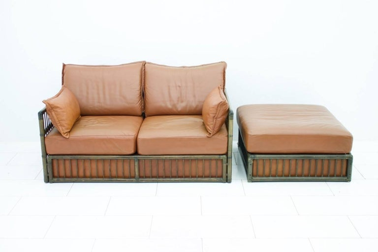 Beautiful leather sofa with loose cushions and rattan frame and a foot stool by Rolf Benz, 1978