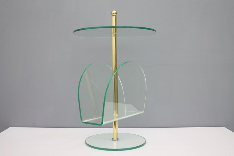 Nice side table from the 1980s. Glass, brass and Lucite in a very good condition. The magazine rack is in Lucite, the base and the tabletop in glass. Very good condition.