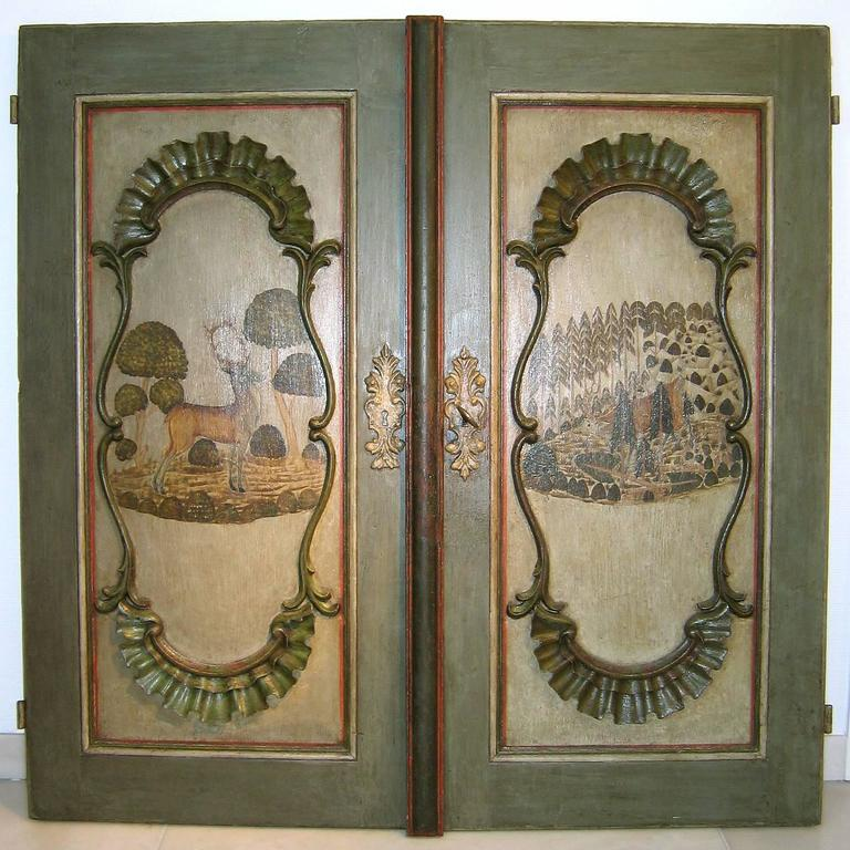 Very charming pair of German painted Baroque cupboard doors from the 18th century, most probably from Bavaria. Original and well preserved paint and rocaille carving, pine wood, original hinges, lock and key. On the backside above the lock dated