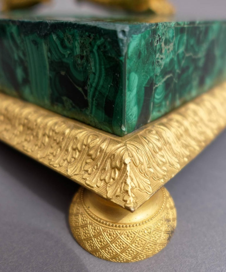 A very fine Russian giltbronze mounted malachite veneered inkstand from the first quarter of the 19th century. Of rectangular form with an acanthus leave decorated border on round feet. Two swans are supporting the cut glass bottles. This is an