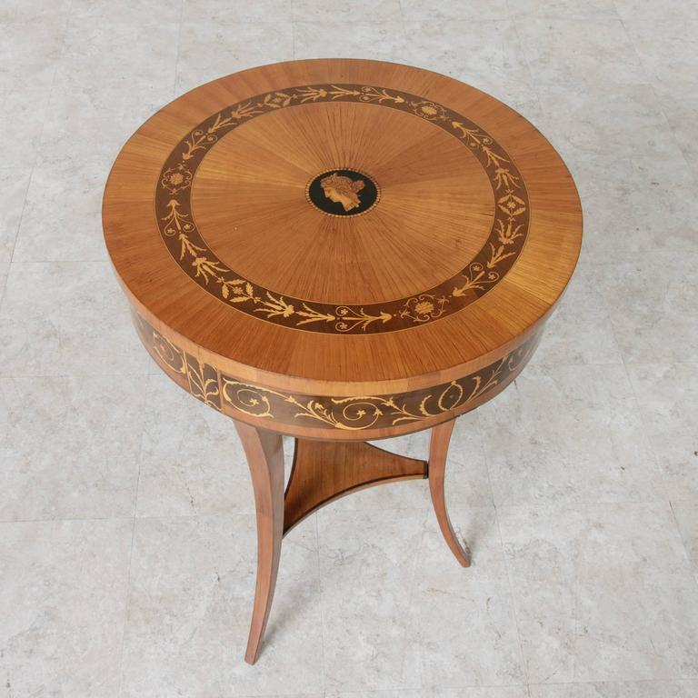 A stunning rare find! This Biedermeier period vanity table from Austria showcases a lemonwood marquetry top in a sunburst pattern. Its central ebony medallion features an inlaid Grecian profile of a classic female figure. A band of sycamore wood