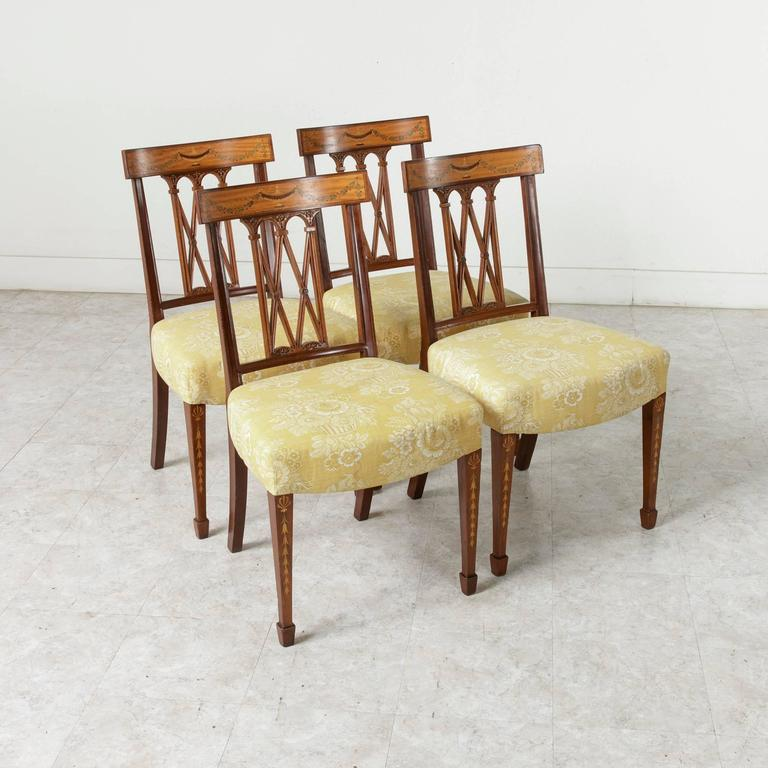 A stunning set of four walnut Italian dining chairs from the 19th century. Intricate inlay of a Classic urn and festooning garland in lemonwood and sycamore grace the curved crown of the hand-carved lattice seatbacks. The marquetry garland motif is
