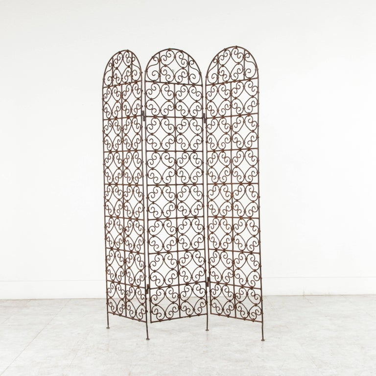 With an intricate hand-forged scrolling pattern, this early 20th century iron folding screen or partition is composed of three panels, each with an arched top. Acquired by a Frenchman in Morocco during the French Colonial period, this artisan-made