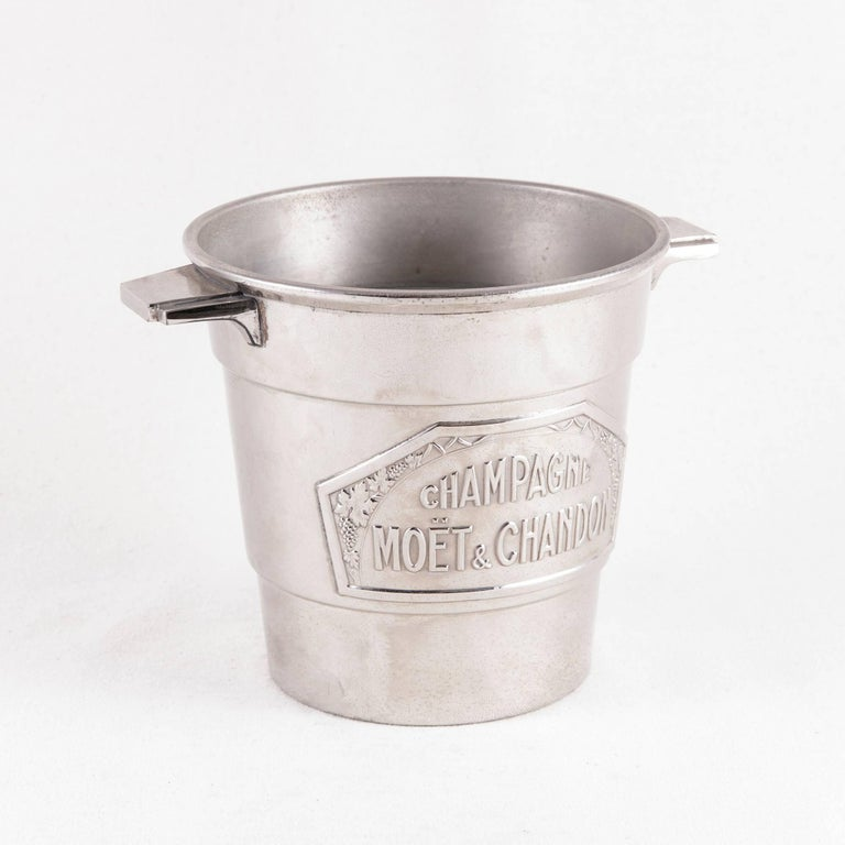 This small-scale Art Deco period silver plate champagne bucket features a label of the name of the renowned champagne producer, Moet et Chandon, flanked by grapes and grape leaves. With its unusual size intended for half bottles of champagne, this